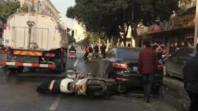 摩托摔倒,司机倒在洒水车车轮前…