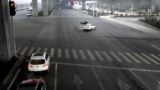 抢黄灯遇上闯红灯,轿车撞飞电动车