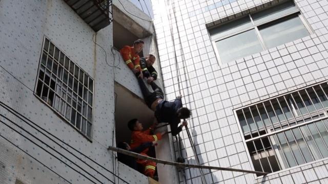男子倒挂楼外,坠落瞬间被消防拉回