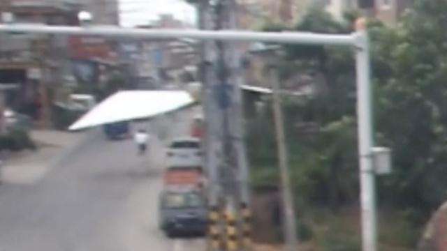 台风吹掉广告牌,车主3秒逃离车被砸