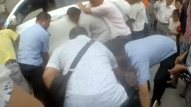 老人被卷车底,警民合力抬车救人