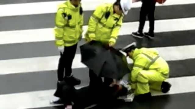 老人被掉落水瓶砸倒,民警撑伞遮雨