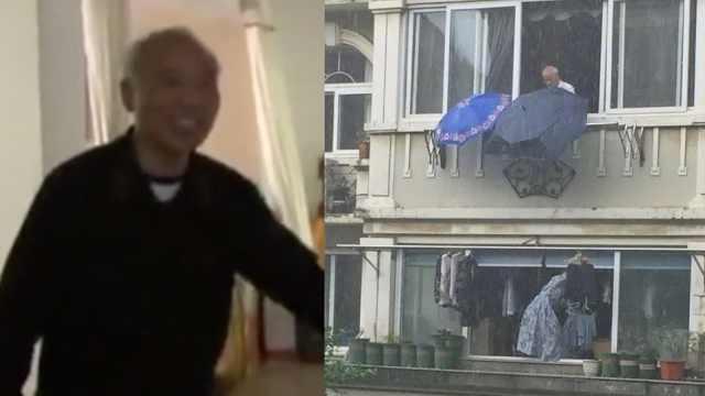 暖!大爷阳台撑伞,替楼下衣物遮雨