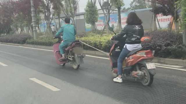 纤夫的爱?摩托男竟绳牵电驴去上班