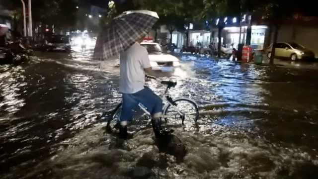暴雨冲开井盖,2市民雨中轮流站岗