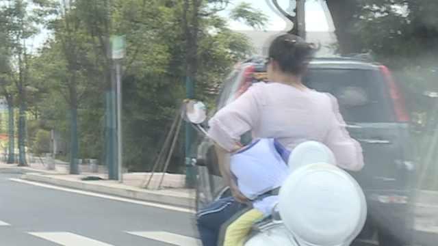揪心!妈骑车娃睡着,单手护住绑身上