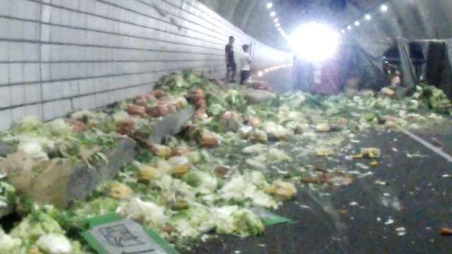 货车侧翻隧道变菜市,司机:路上有坑