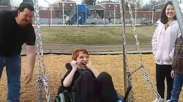 10岁轮椅男孩第一次荡秋千笑容灿烂