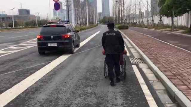 男子前行困难,特警推着轮椅护送