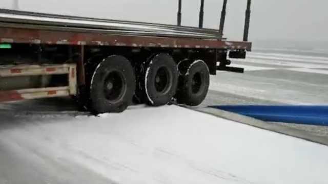 雪天路滑!货车尾部悬桥墩,民警急救