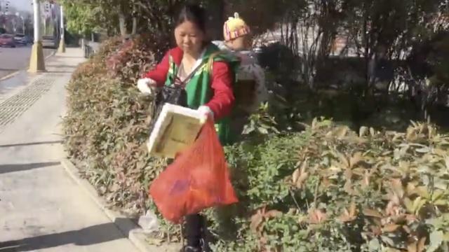 环卫工背1岁女儿捡垃圾,当街喂奶