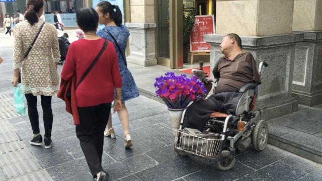 卖花残疾人街头呼呼大睡,称没生意
