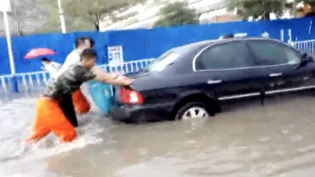 暴雨突袭道路成河:车抛锚,人被困