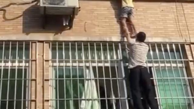 女童找妈妈悬挂窗外,大叔爬窗托举