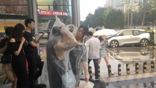 暖!突降暴雨,北京地铁哥免费发雨衣