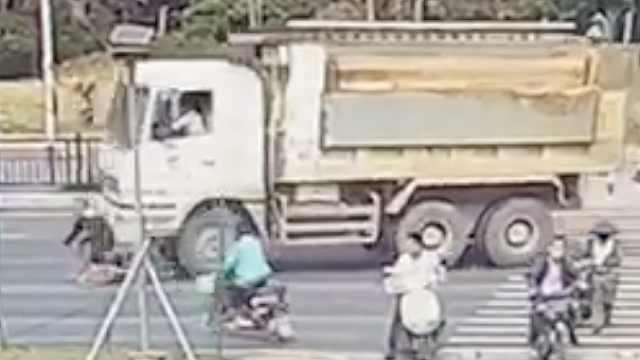 男子骑车泥头车前穿行,遭撞趴碾轧