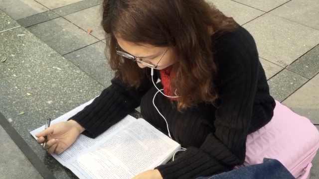 女生为考英语专八,火车站坐地复习