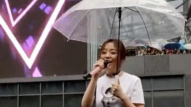 张靓颖重庆商演遇雨,撑伞唱