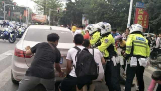 骑车女子卷车底,警民合力抬车救人