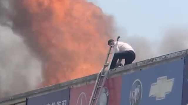 汽配城突发大火,他爬房顶冒险扑救