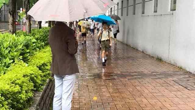 下雨天,小学校长门口撑伞迎接学生
