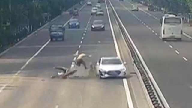 他载老伴横穿马路,被超速轿车撞飞