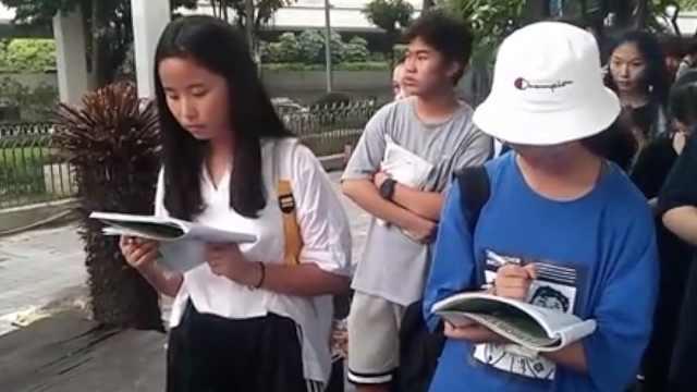 初中女生看演唱会,边排队边写作业