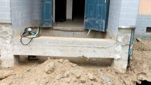 居民楼四周泥土坍塌,楼门口现大坑