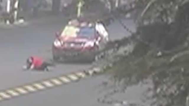 打着电话横穿马路,红衣女被车撞翻