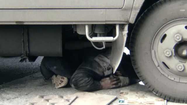 司机斜坡上修车,不料溜坡碾压自己