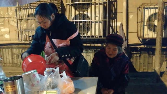 女子摆摊带着婆婆:她耳聋方便照顾