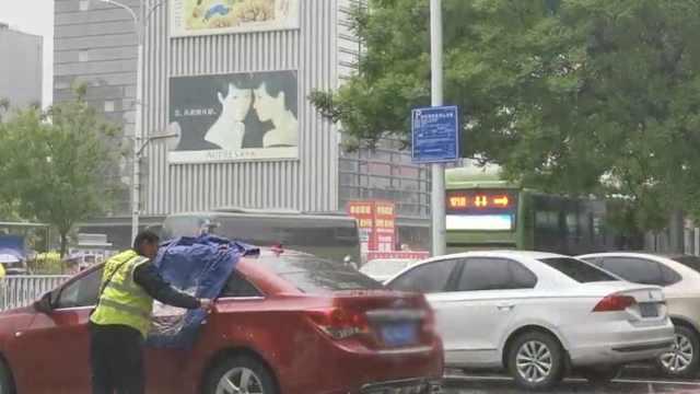 他停车忘关窗,突下雨大叔脱衣遮挡