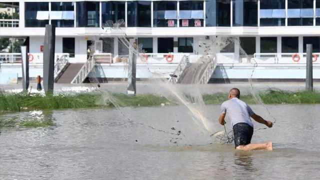 洪水进入南宁城区,市民在公园捕鱼