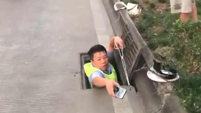 交警只身钻窨井,只为帮市民捞手机