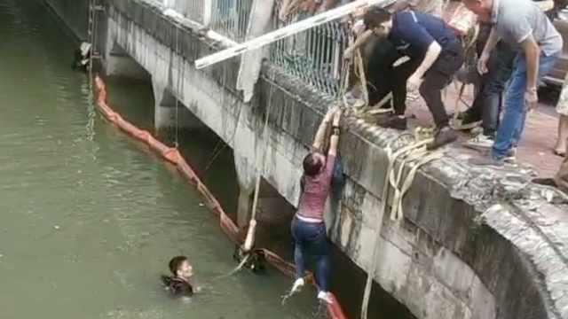 小车冲破护栏栽进河里,路人拉绳救起落水者