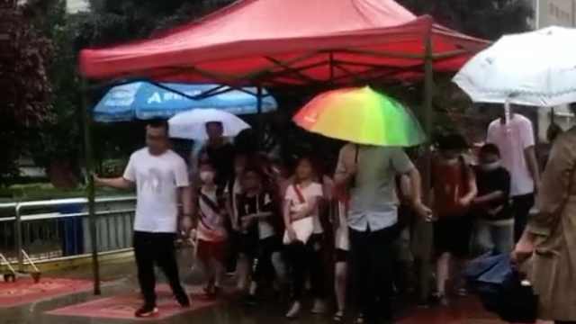 下雨天小学老师举雨棚护送学生放学,家长:好