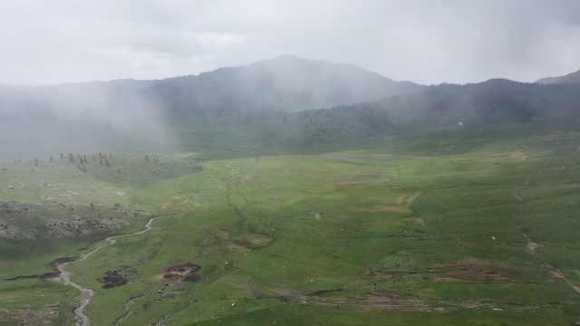 冬夏同框!新疆草原边出太阳边下雪,山峦两侧呈现截然不同美景
