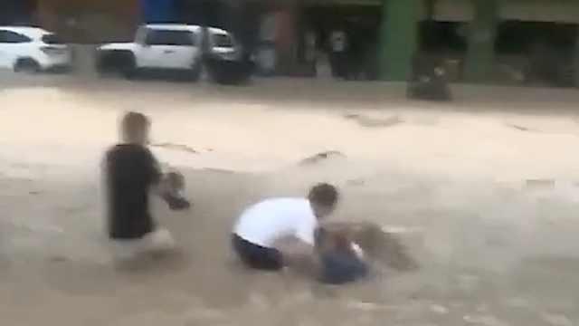 54岁校长冲进水流拉住遇险女子:没觉得年龄大,直接冲下去