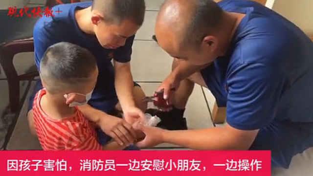 熊孩子手指卡玩具,消防员边哄孩子边救助