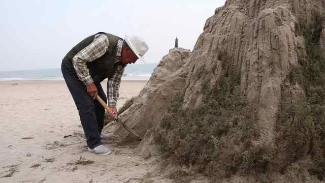 8旬大爷在海边用沙造山坚持6年,雕塑比人高,能坚持一周不倒